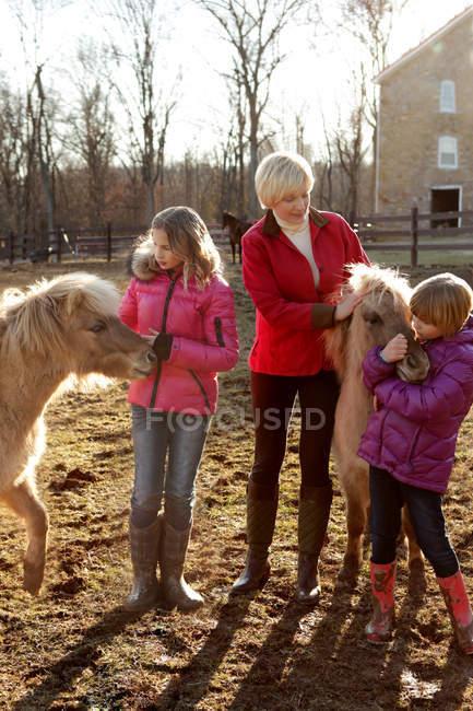 Madre y dos hijas, al aire libre, de pie con ponis - foto de stock
