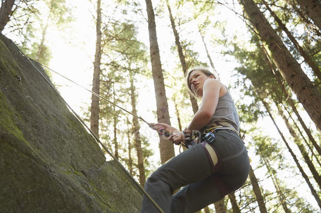 Low angle view of Rock climber scaling rock — Stock Photo
