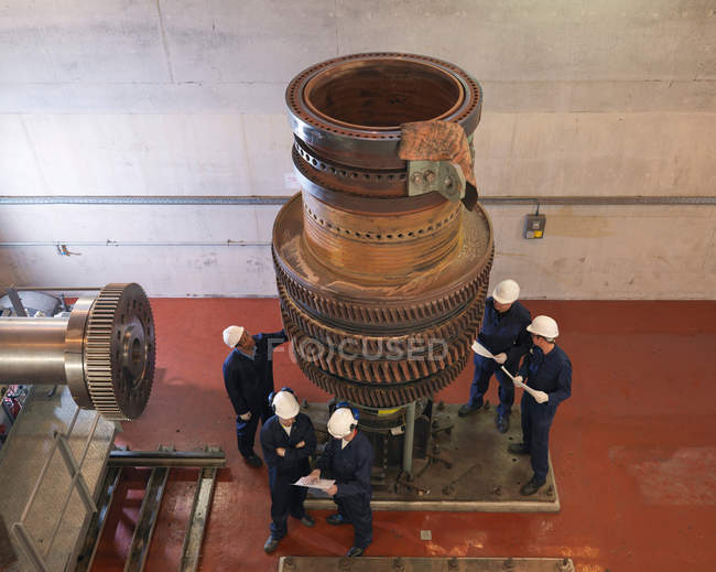 Высокоугловый вид инженеров, работающих на турбинах — стоковое фото