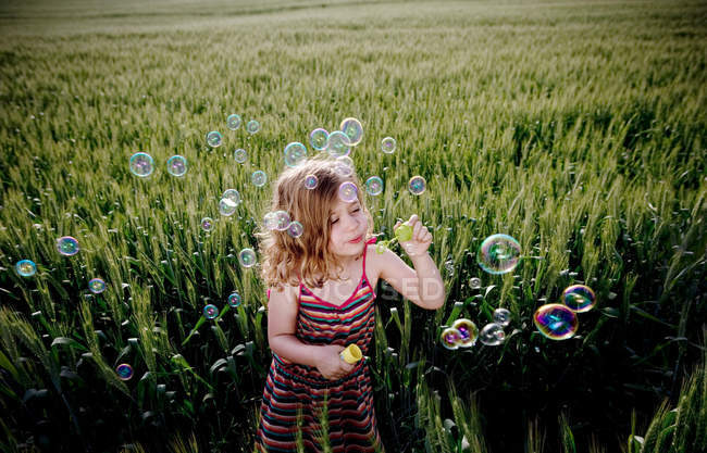 Girl blowing bubbles in wheat field — Stock Photo