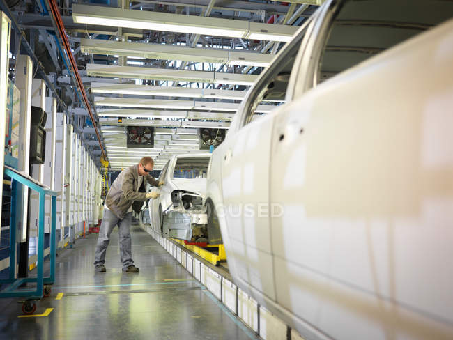Робітник заводу автомобіля на лінії виробництва — стокове фото