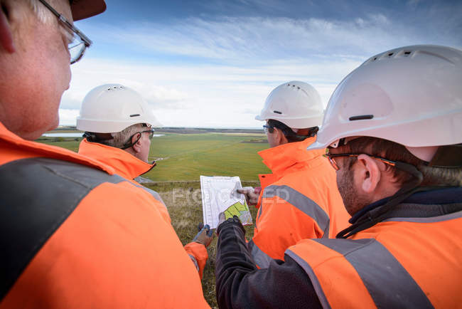 Workers holding plans inspecting land around surface coal mine restoration — Stock Photo