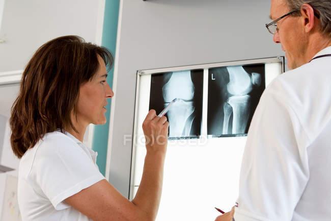 Médico e enfermeira examinar radiografias — Fotografia de Stock