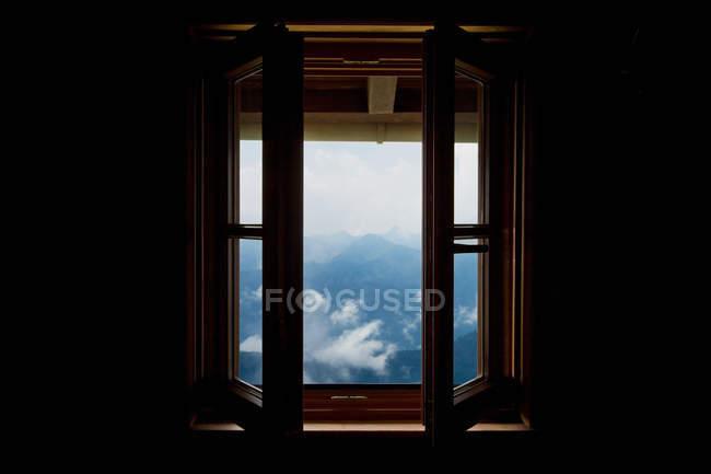 Vista a través de ventana abierta al paisaje de montaña - foto de stock