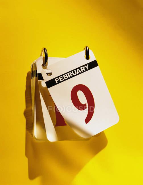 Перевернуть календарь, висящий на ярко-желтой стене — стоковое фото