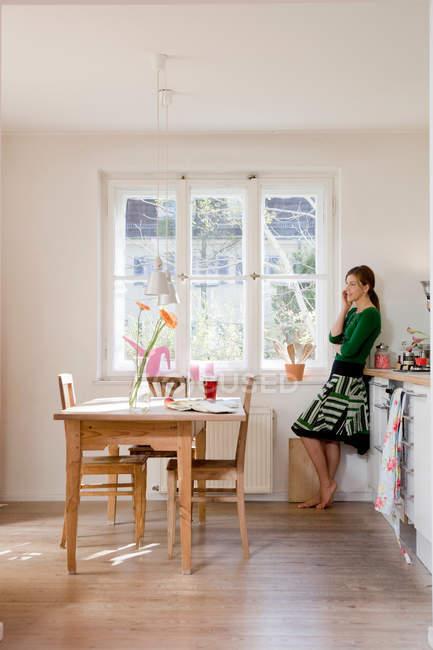 Mujer en la cocina hablando por teléfono — Stock Photo