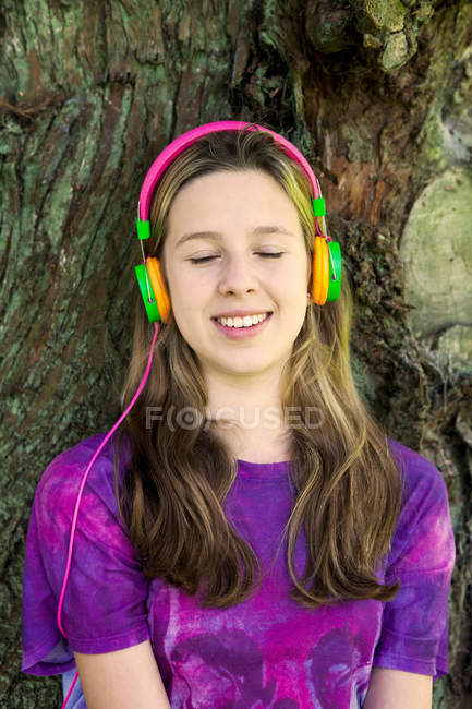 Girl listening to headphones in park — Stock Photo