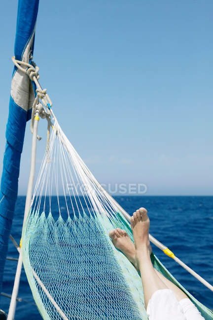 Woman's feet in hammock on sailing boat — Stock Photo