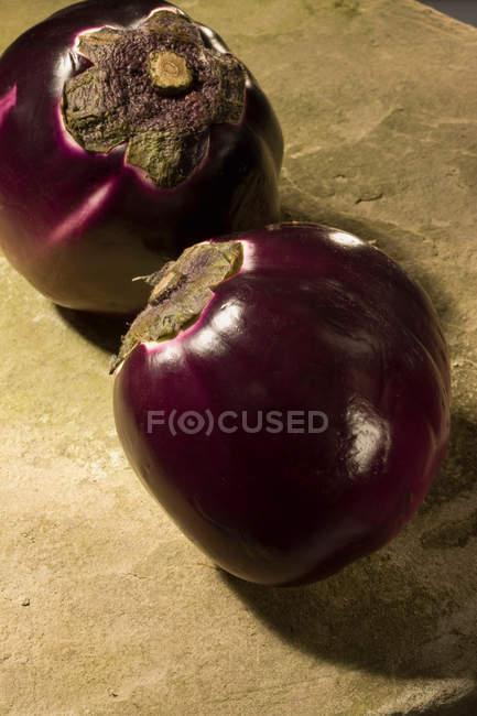 Deux aubergines en plein soleil sur la surface du béton — Photo de stock