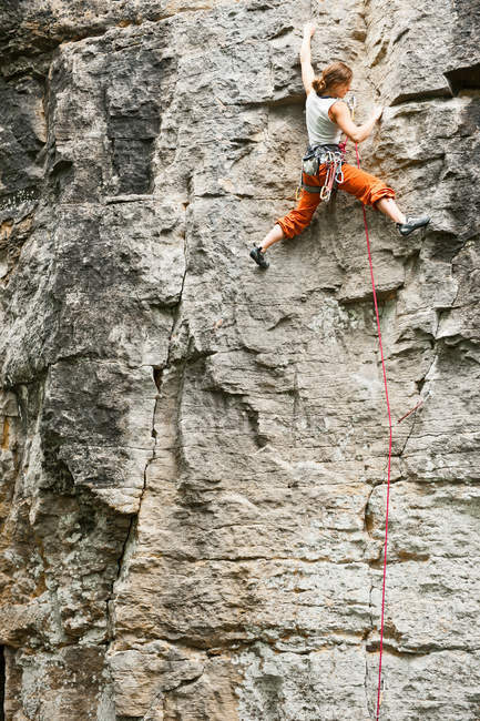 Climber scaling steep cliff face — Stock Photo