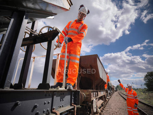 Railway workers wearing high visibility clothing on train — Stock Photo