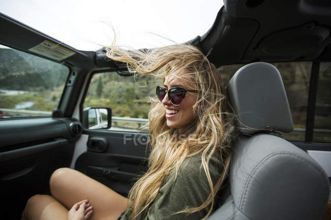Young woman with windswept long blond hair on the road in jeep — Stock Photo