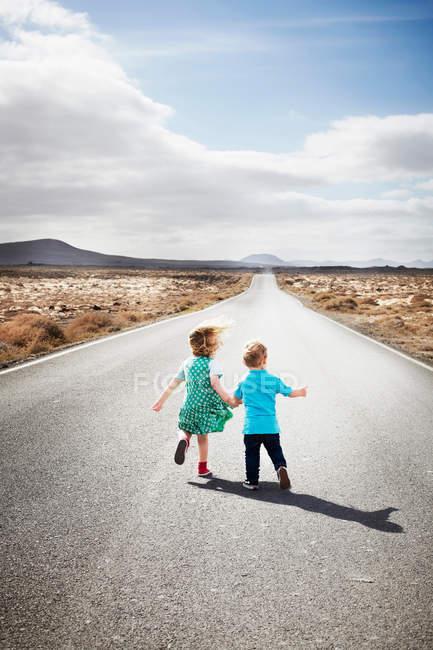 Niños caminando por el camino rural pavimentado - foto de stock