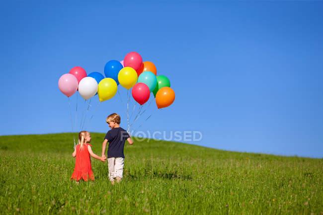 Дети с разноцветными воздушными шарами в траве — стоковое фото