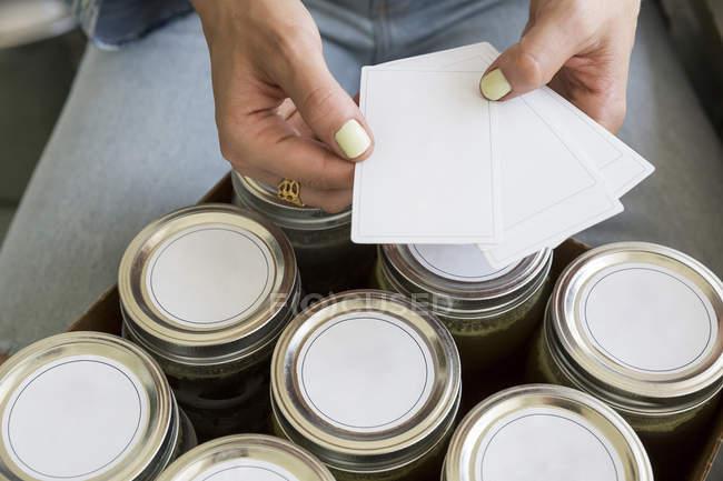 Vista recortada de los tarros de etiquetado de la mujer - foto de stock