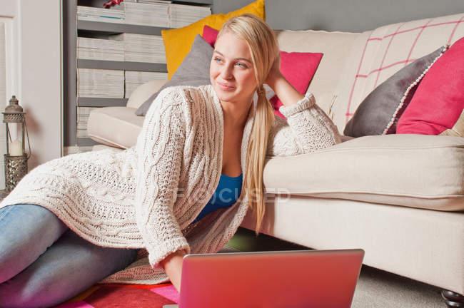 Donna che utilizza laptop e sognare ad occhi aperti a casa — Foto stock
