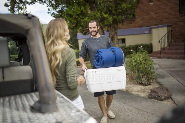 Young couple preparing jeep for road trip — Stock Photo