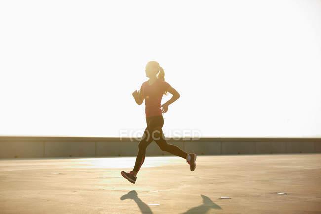 Женщина бежит по крыше на рассвете — стоковое фото