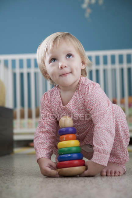Female toddler playing with stacking toy — Stock Photo