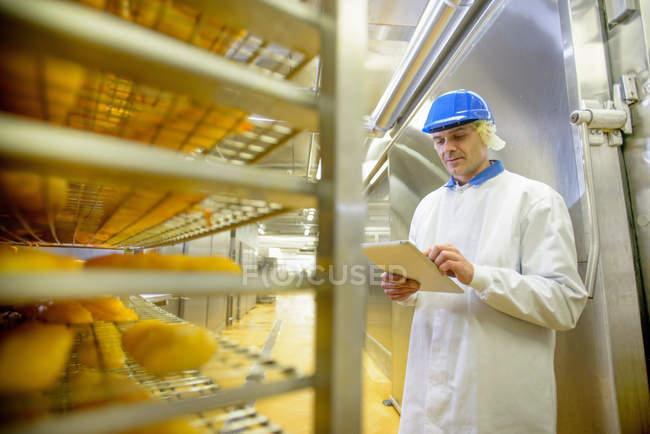 Працівник перевірки запасів подробиці на планшеті риб для куріння в харчовій фабриці — стокове фото