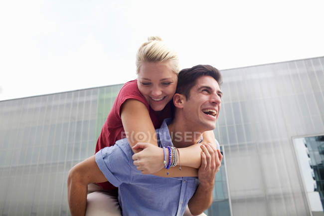 Man carrying girlfriend piggyback — Stock Photo
