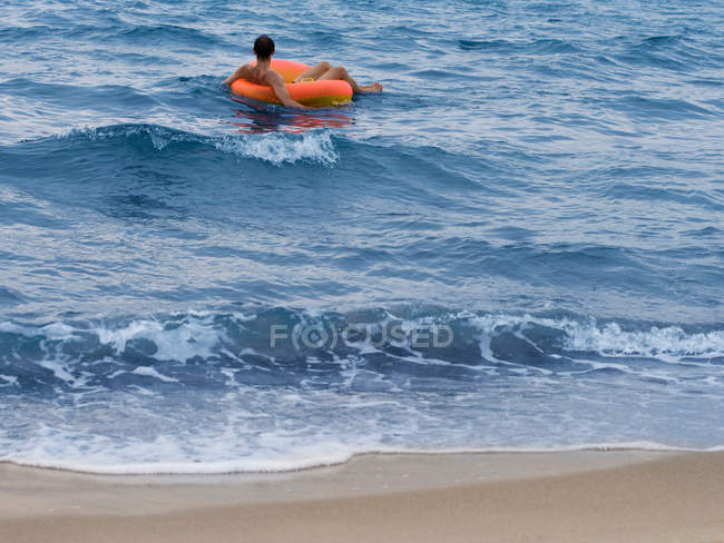 Man floating in inner tube in ocean — Photo de stock
