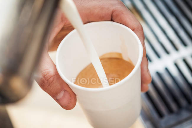Man pouring milk into coffee cup — Stock Photo