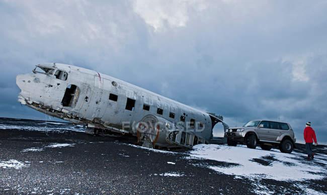 Escursionista esplorare il relitto di aereo in neve — Foto stock