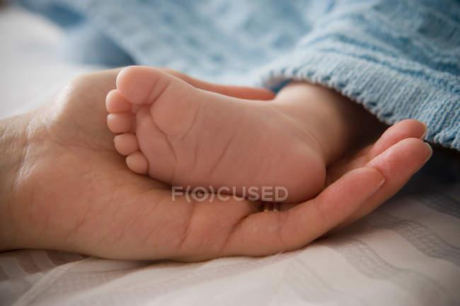 Metà donna adulta tenendo piccolo piede di bambino ragazzo — Foto stock