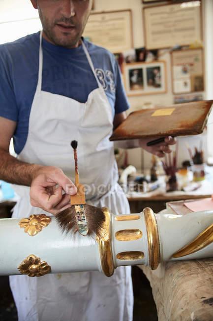 Trabalhador aplicando folha de ouro ao pólo — Fotografia de Stock