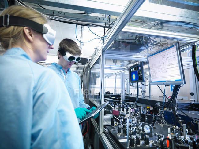 Wissenschaftler durch Monitore mit Laserstrahlprofilen und Laborcode — Stockfoto