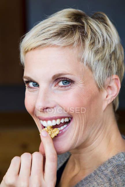 Улыбающиеся женщина ест закуски — стоковое фото
