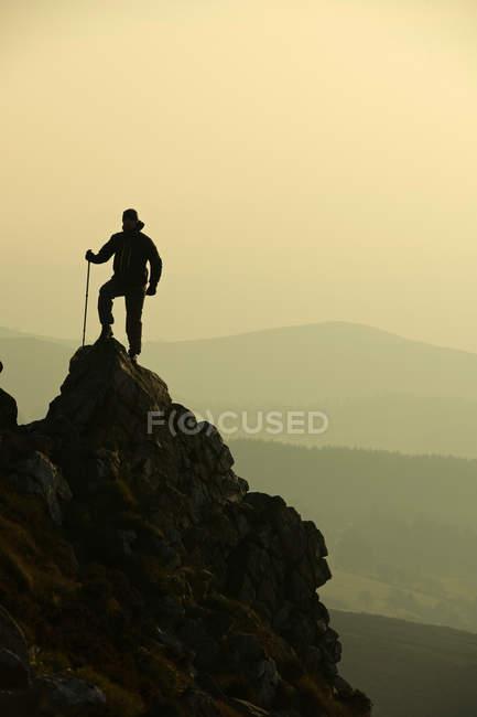 Man hiking on rocky hillside — Stock Photo