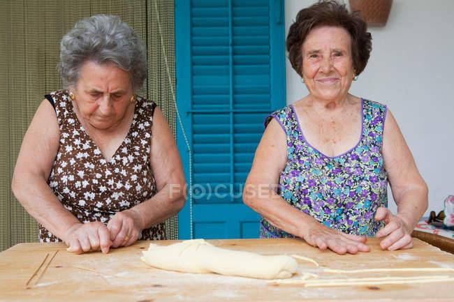 Le donne anziane che fanno la pasta insieme — Foto stock