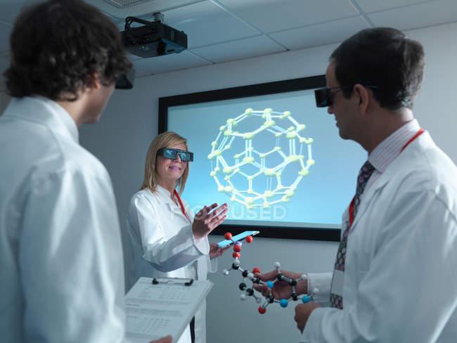 Scientifiques et apprenti dans des lunettes 3D en réunion devant le modèle moléculaire sur l'écran 3D — Photo de stock