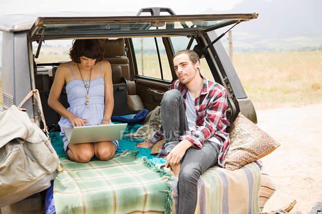 Пара в позашляховик з ноутбуком — стокове фото