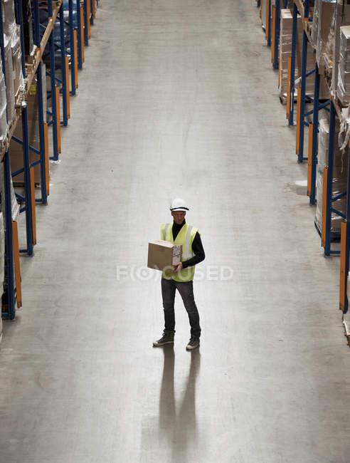 Рабочий с коробкой на складе — стоковое фото