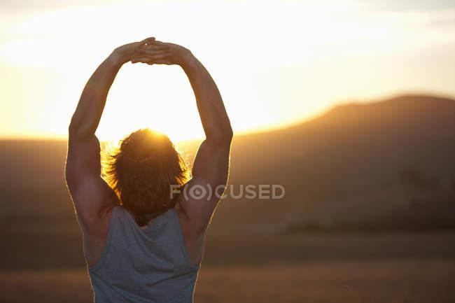 Человек, растянувшийся в поле на закате — стоковое фото