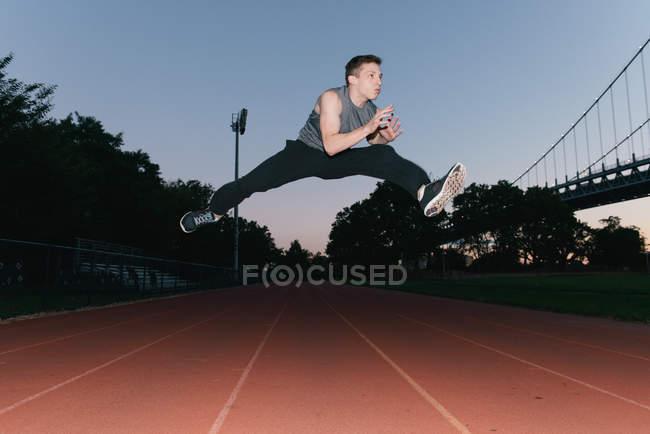 Молодой человек прыгает в воздух, на беговой дорожке, закат, вид с низкого угла — стоковое фото