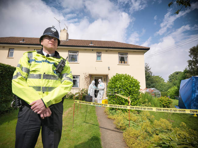Portrait of policeman outside house with forensic scientists in background at crime scene — Stock Photo