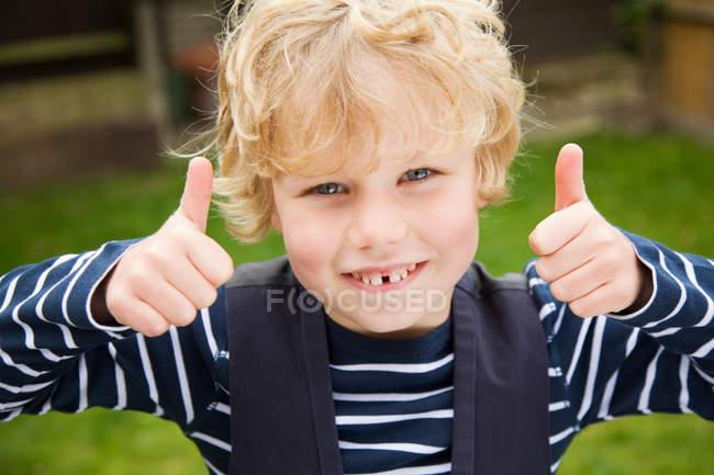 Garçon souriant donnant pouces en plein air — Photo de stock