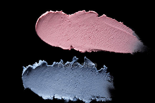 Smeared blue and pink eyeshadow on black background — Stock Photo