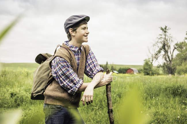 Вид збоку підліток хлопчик в поле носіння плоскою кришкою, притулившись відділення дивлячись геть посміхається — стокове фото