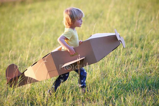 Garçon volant avion en carton à l'extérieur, se concentrer sur l'avant-plan — Photo de stock