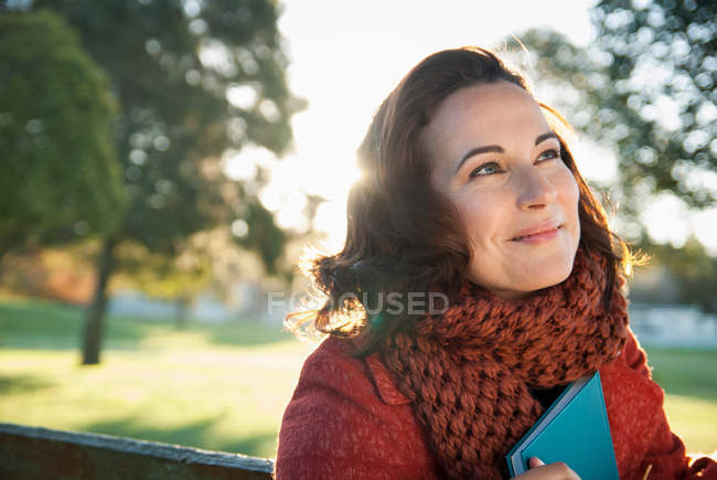 Smiling woman holding book outdoors — Stock Photo