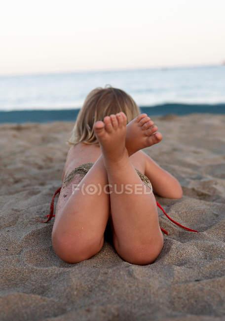 Visão traseira da criança fêmea que coloca na praia — Fotografia de Stock