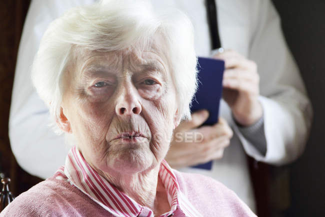 Older woman frowning face, focus on foreground — Stock Photo