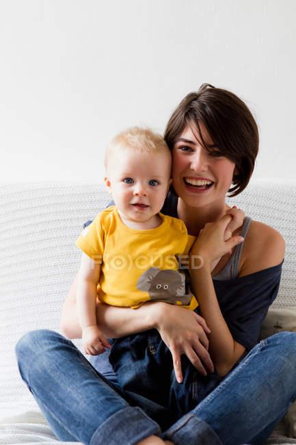 Mamma e bambino seduti sul letto — Foto stock