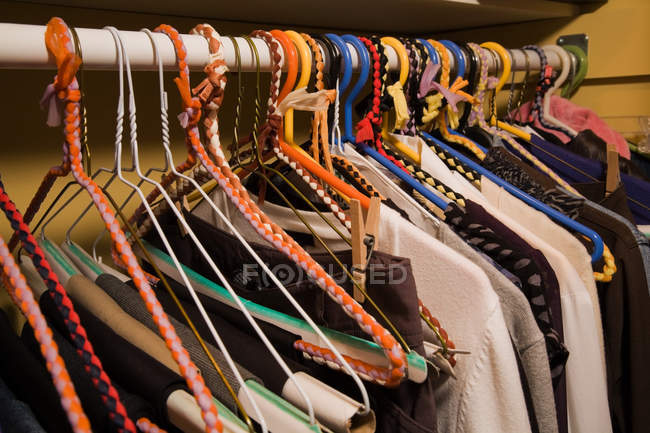 Clothes on colorful hangers in closet — Stock Photo