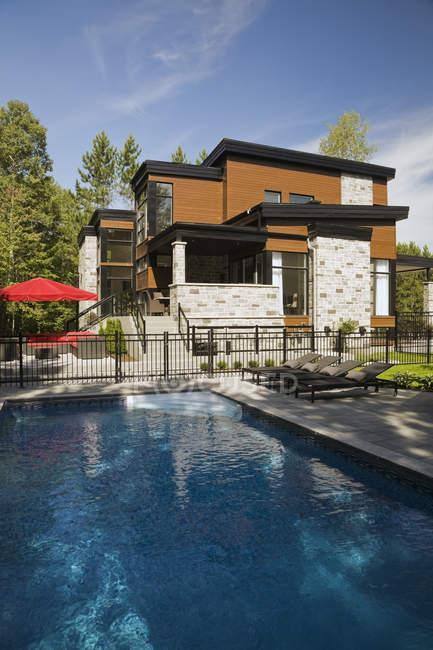Розкіш бежевий камінь і дерев'яного будинку з садом та плавальним басейном — стокове фото